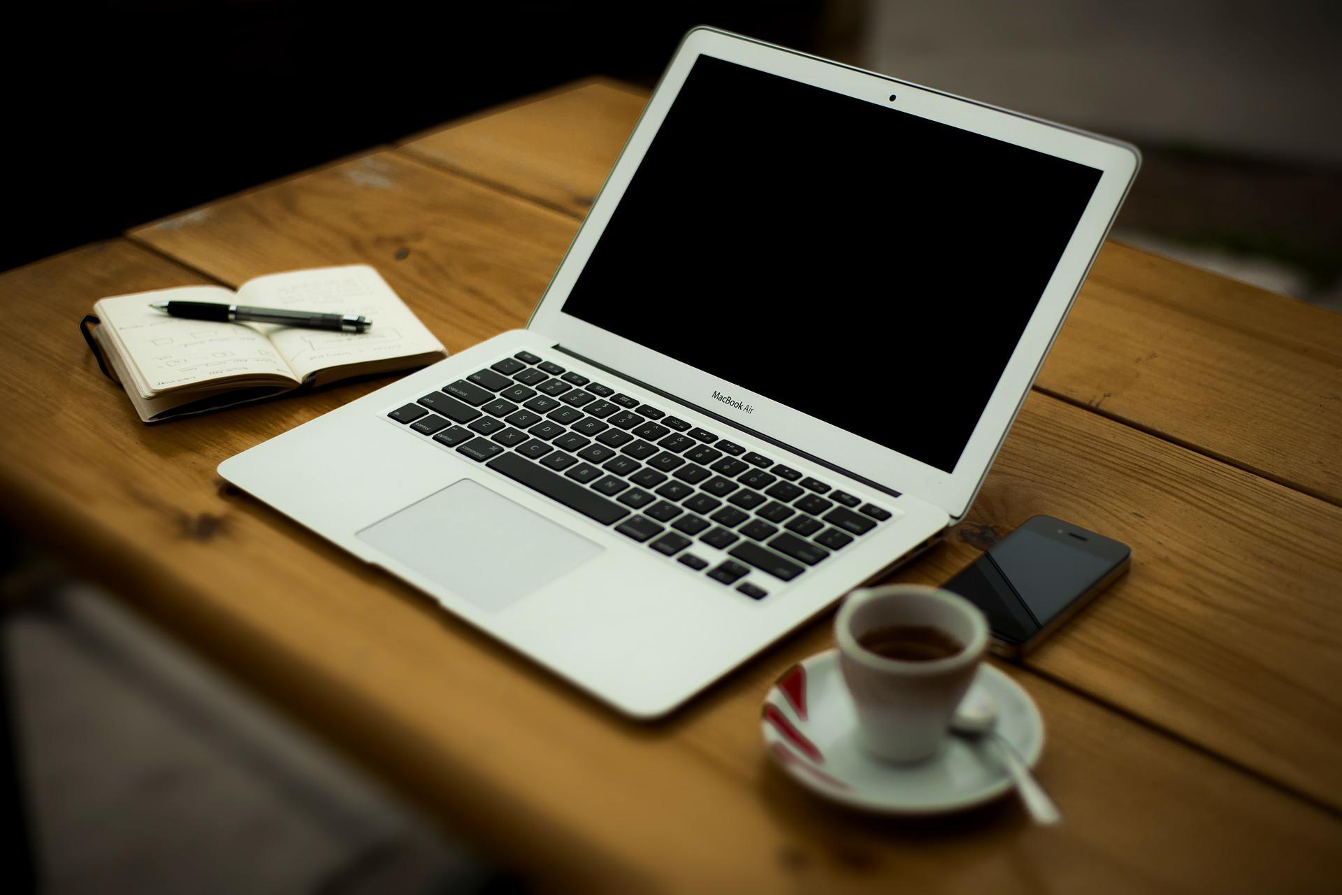 Un tavolo con un porattile, una tazzina di caffè, un cellulare e un quaderno