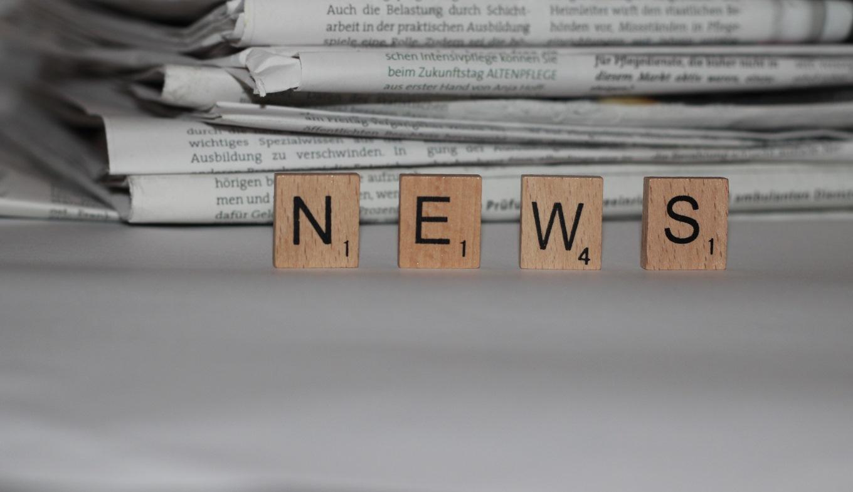 Pila di quotidiani con le lettere della parola news in primo piano