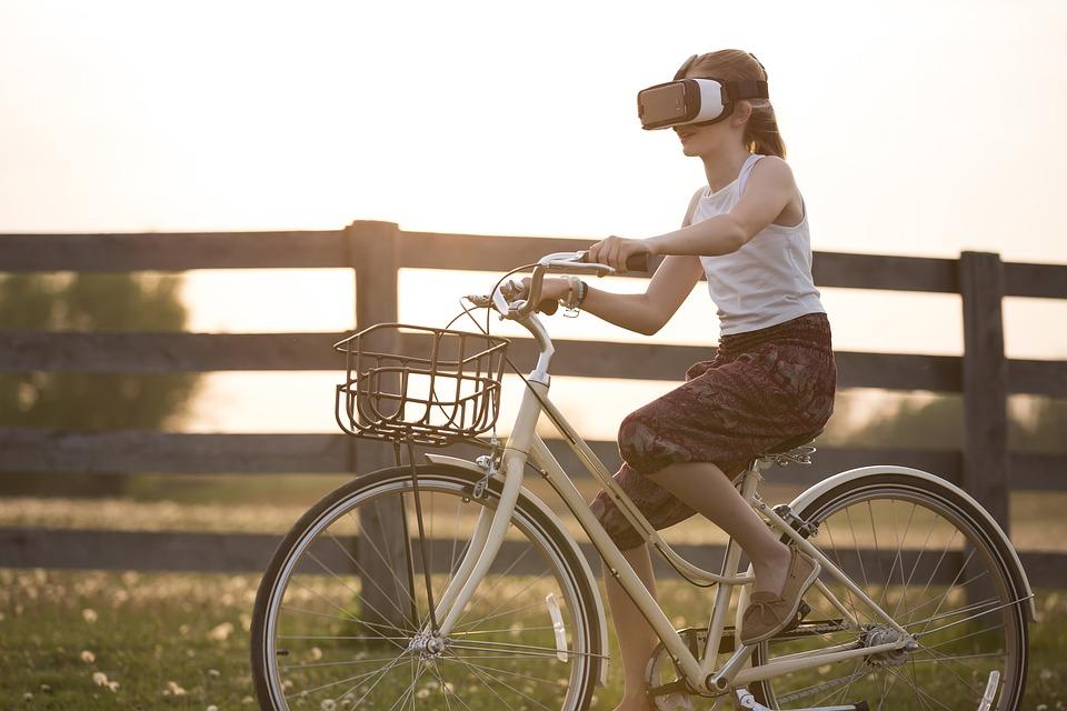 ragazza corre in bicicletta con l'aiuto della realtà virtuale