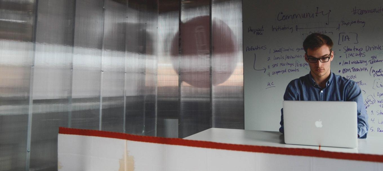 Un ragazzo lavora al pc in un ufficio di una startup innovative