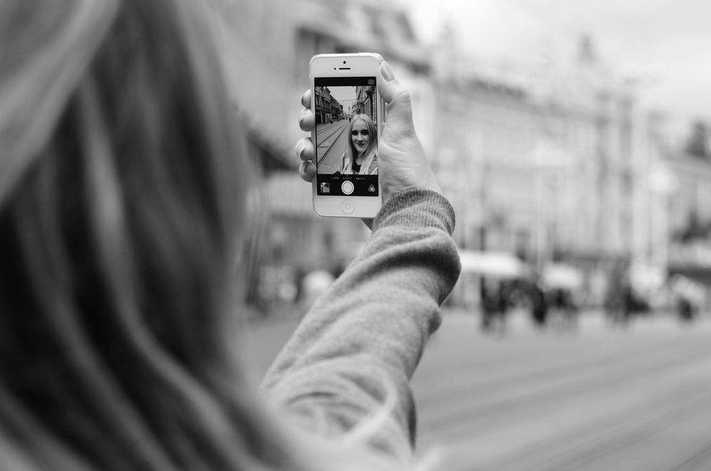 Una ragazza si scatta un selfie in una strada di città