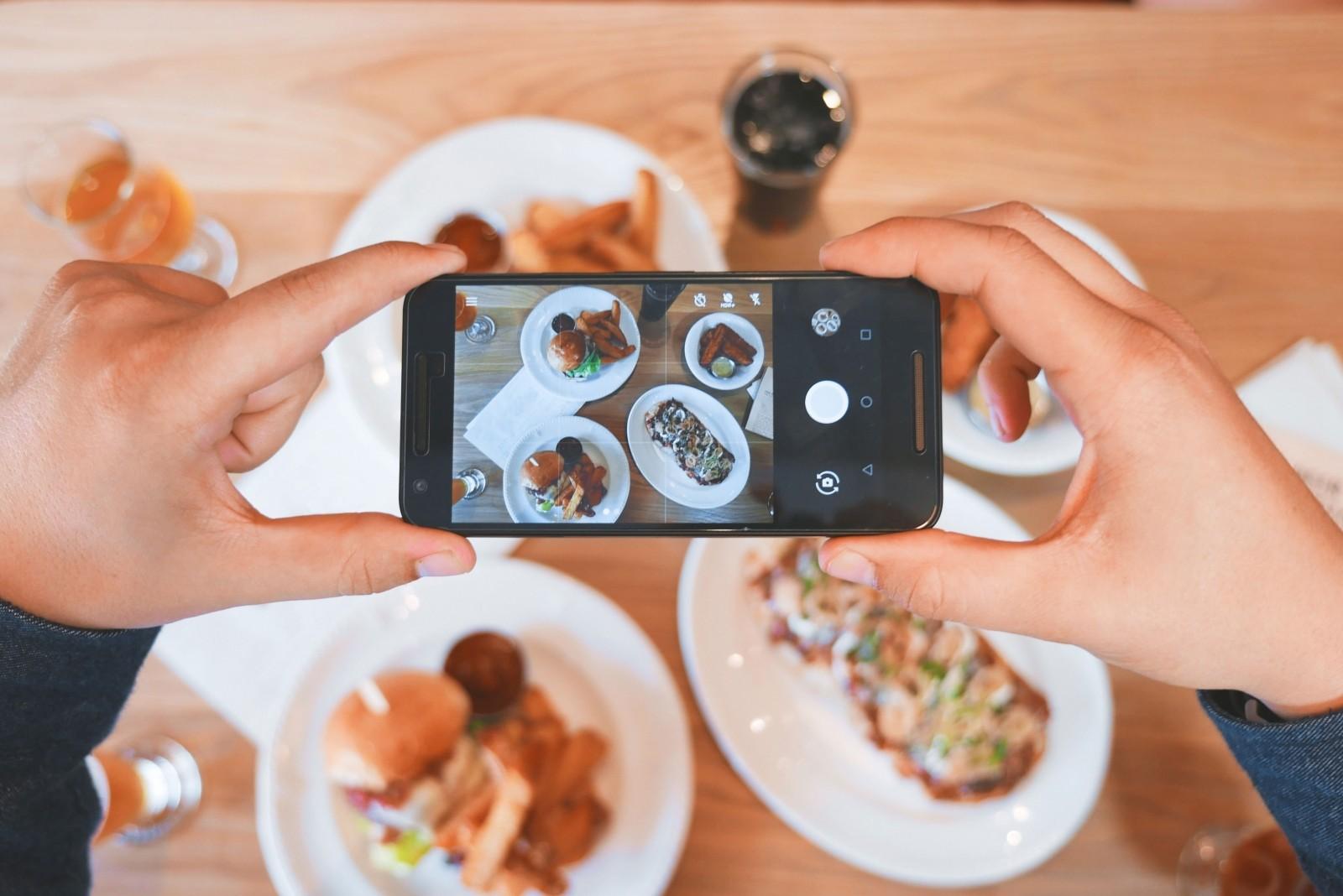 Smartphone che scatta una foto ad una tavola piena di cibi e piatti per condividerla su Instagram