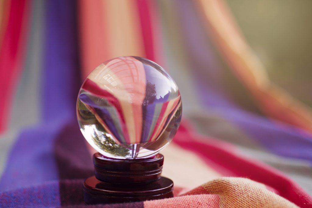 Una sfera di cristallo per predire il futuro poggiata su una base di legno
