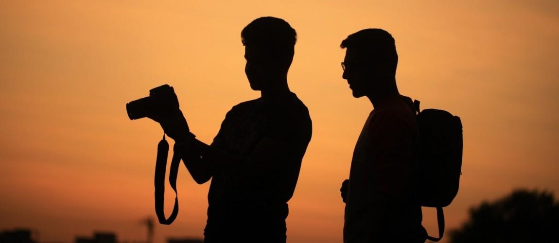 visual content: immagine di due persone con macchina fotografica su sfondo panoramico arancione