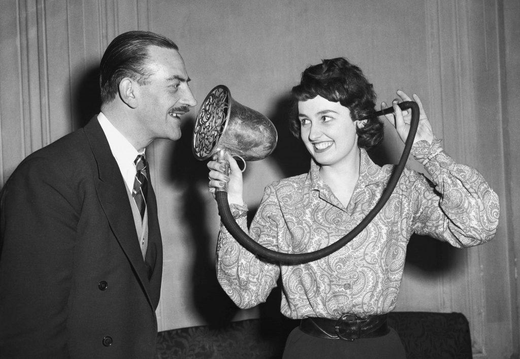 Un uomo parla ad un amplificatore che è collegato all'orecchio di una donna