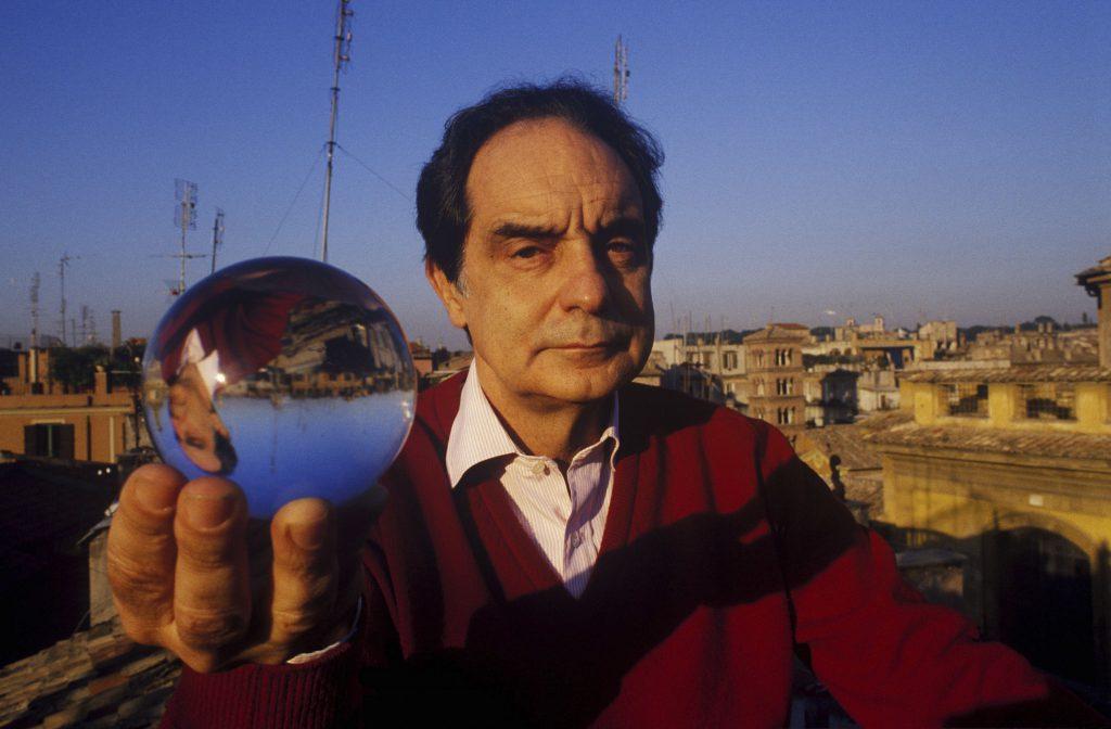 Lo scrittore Italo Calvino tiene in mano una sfera di cristallo