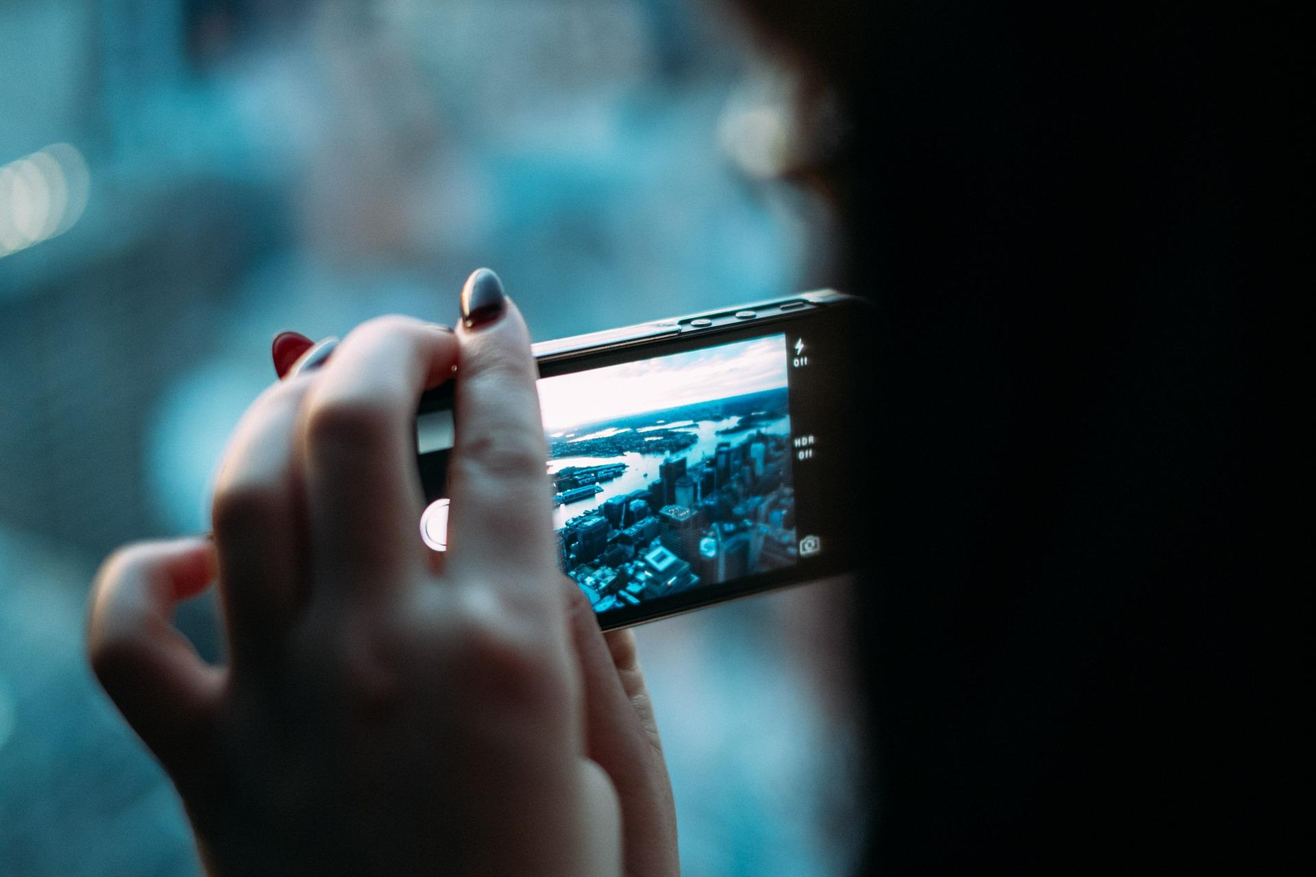 una ragazza scatta una foto con il cellulare. l'algoritmo di instagram poi la renderà visibile