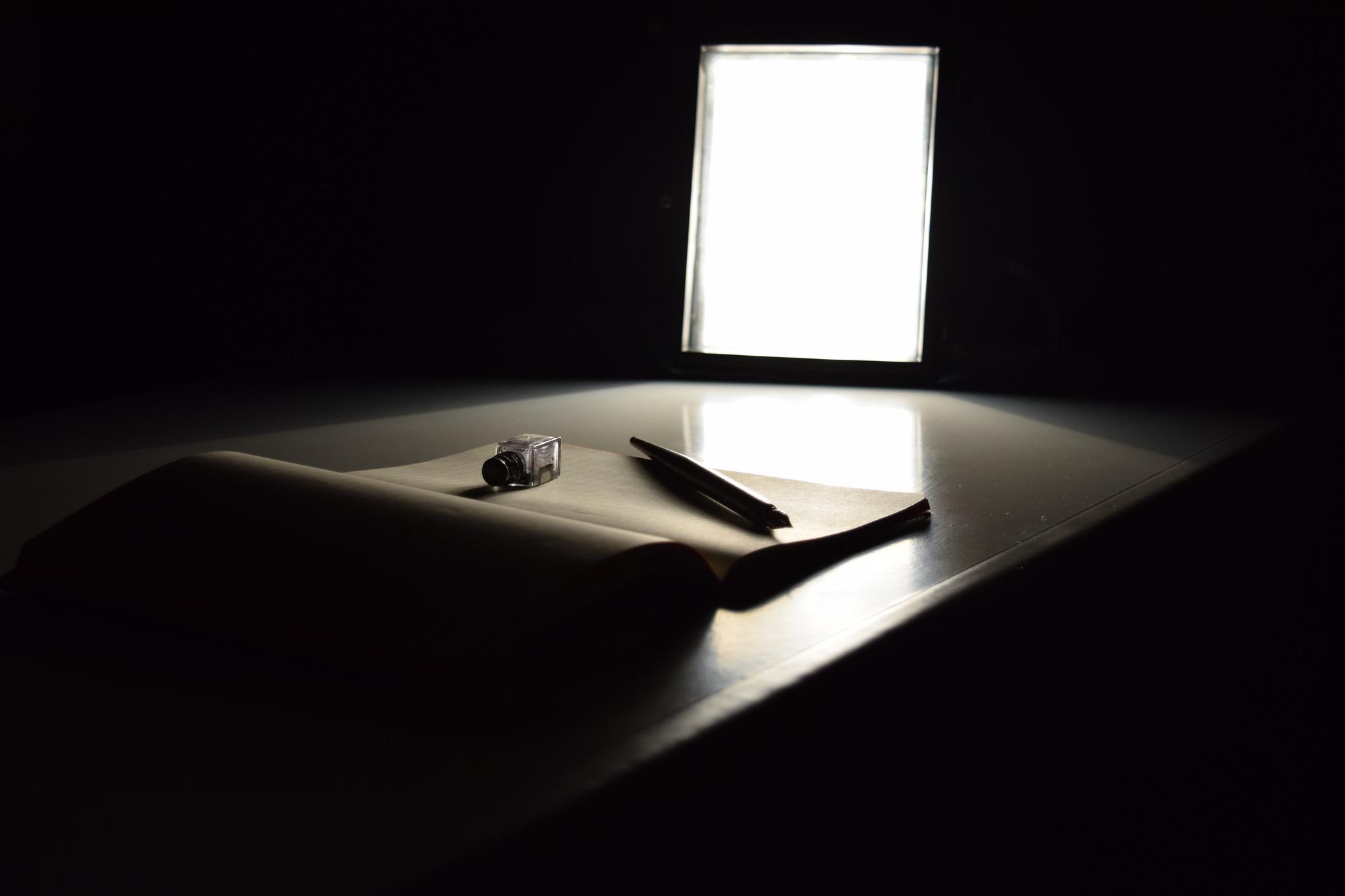 Una penna poggiata su un quaderno bianco che richiama l'idea del blocco dello scrittore