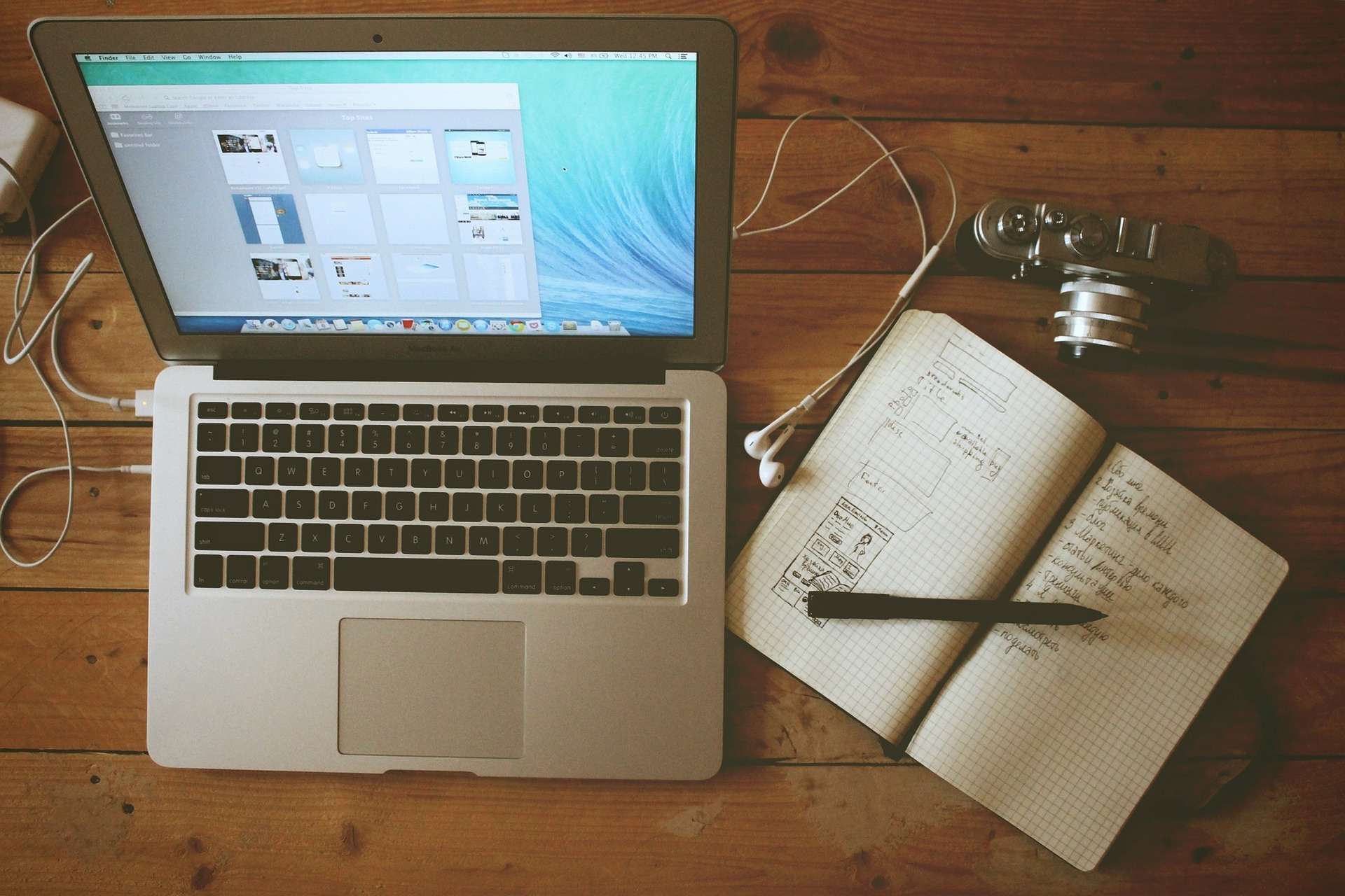 Un mac, un'agenda, una matita, una macchina fotografica poggiati su un tavolo. Tutto il necessario per un blog aziendale