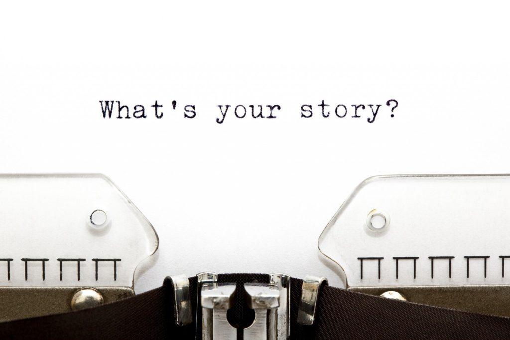 """Una macchina da scrivere dove un foglio riporta la scritta """"what's your story"""""""