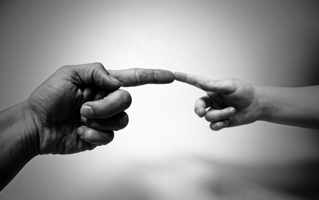La mano di un anziano incontra quella di un bambino