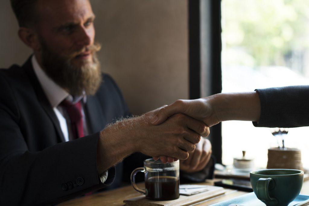Una stretta di mano tra uomini d'affari davanti ad una tazza di caffè