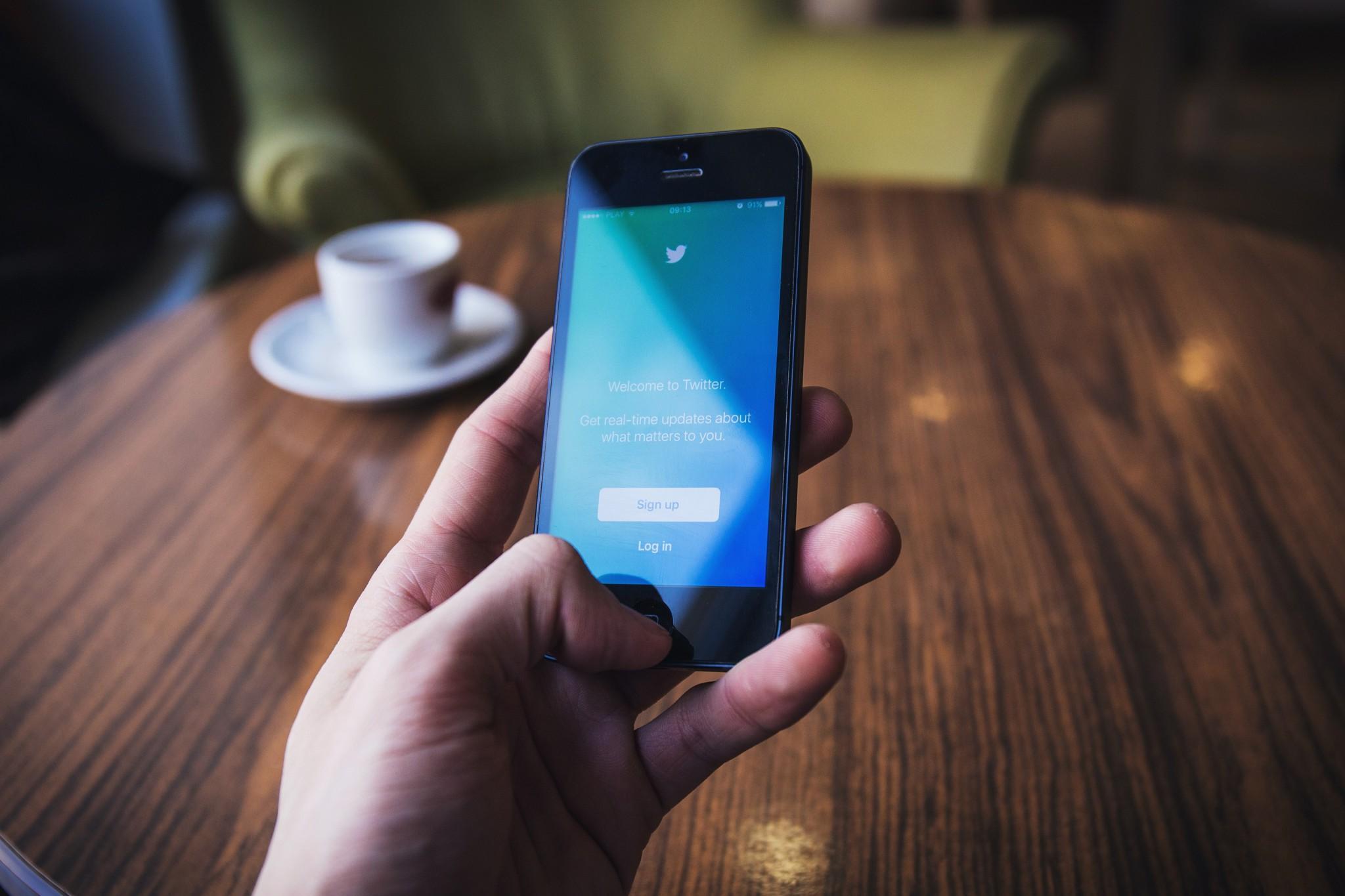 Una mano tiene un cellulare con l'app di twitter durante un live tweeting