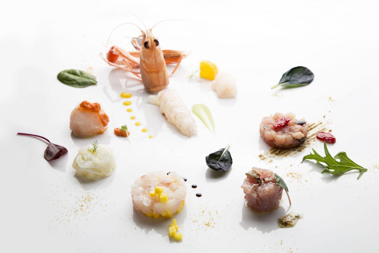 Un piatto bianco con alcuni gamberetti ideale per fare content marketing nella ristorazione