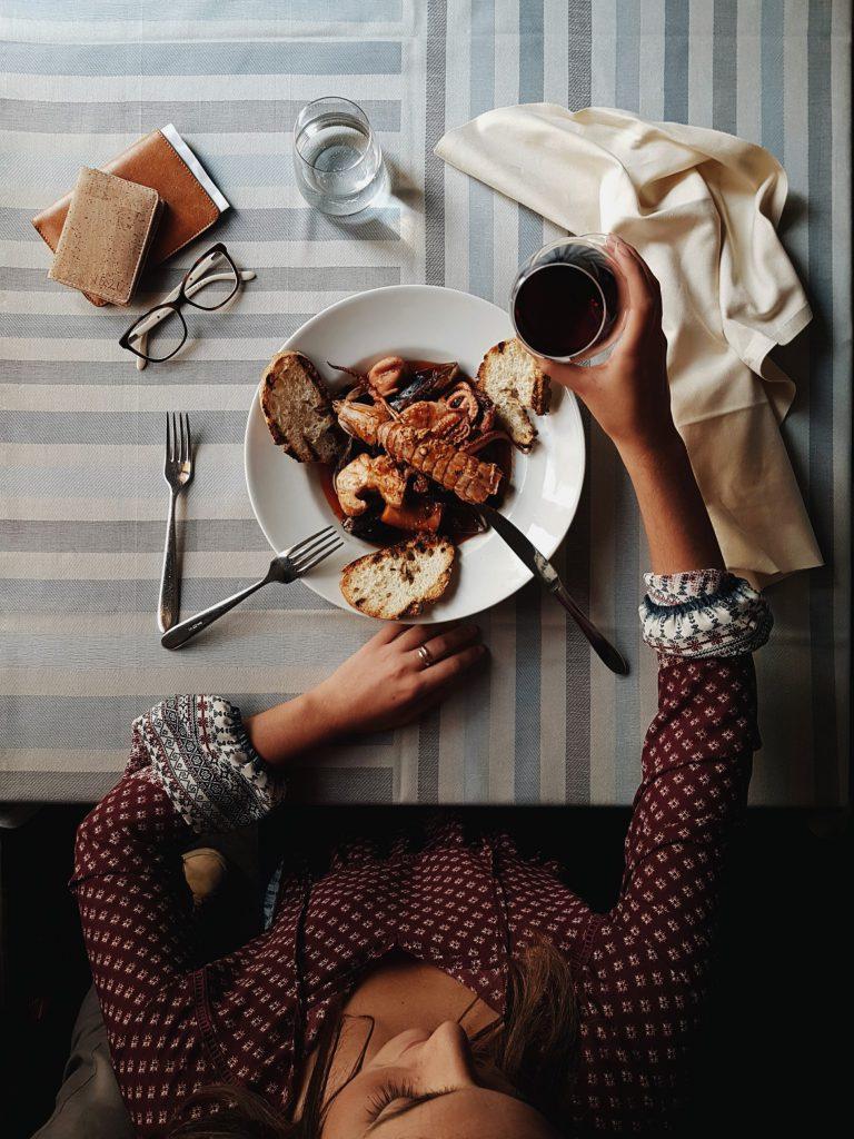 Una ragazza mangia un piatto di cacciucco livornese