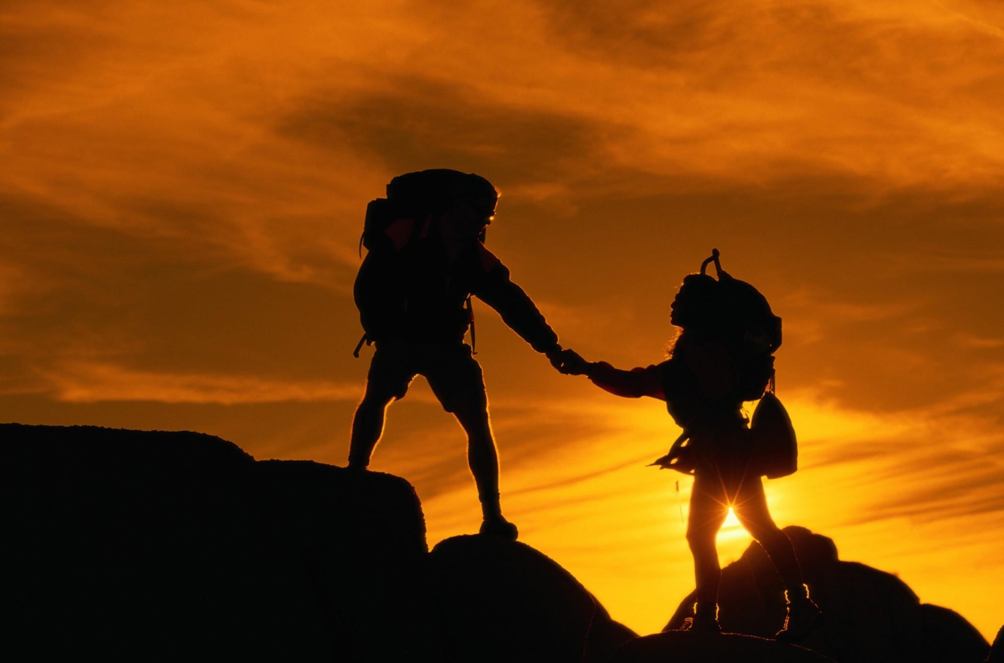 Economia della fiducia nello sport. Due alpinisti si aiutano nella salita su una montagna