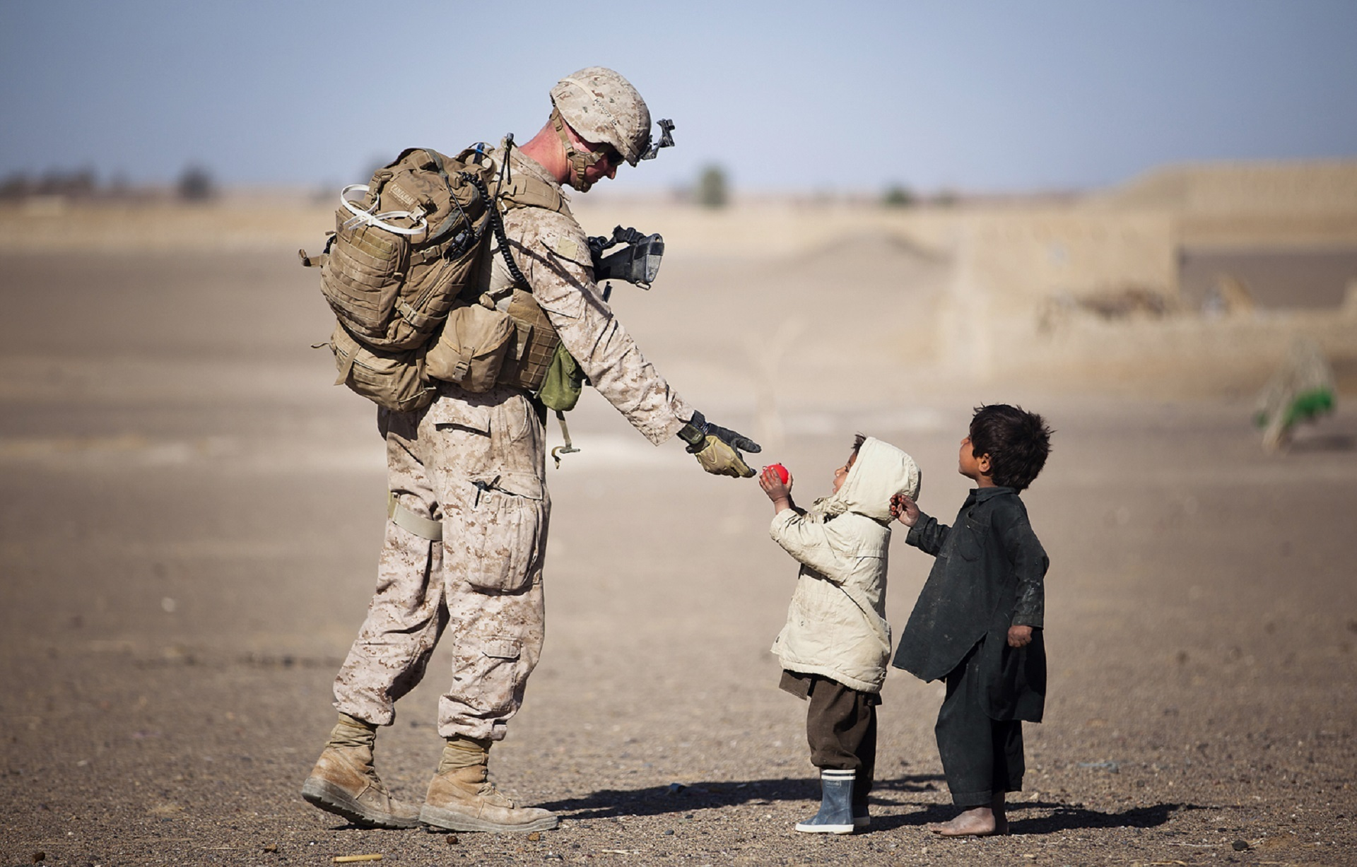 Un soldato dona qualcosa a dei bambini. Questa è una foto che induce alla pre-suasione, che ha molto a che fare con il content marketing