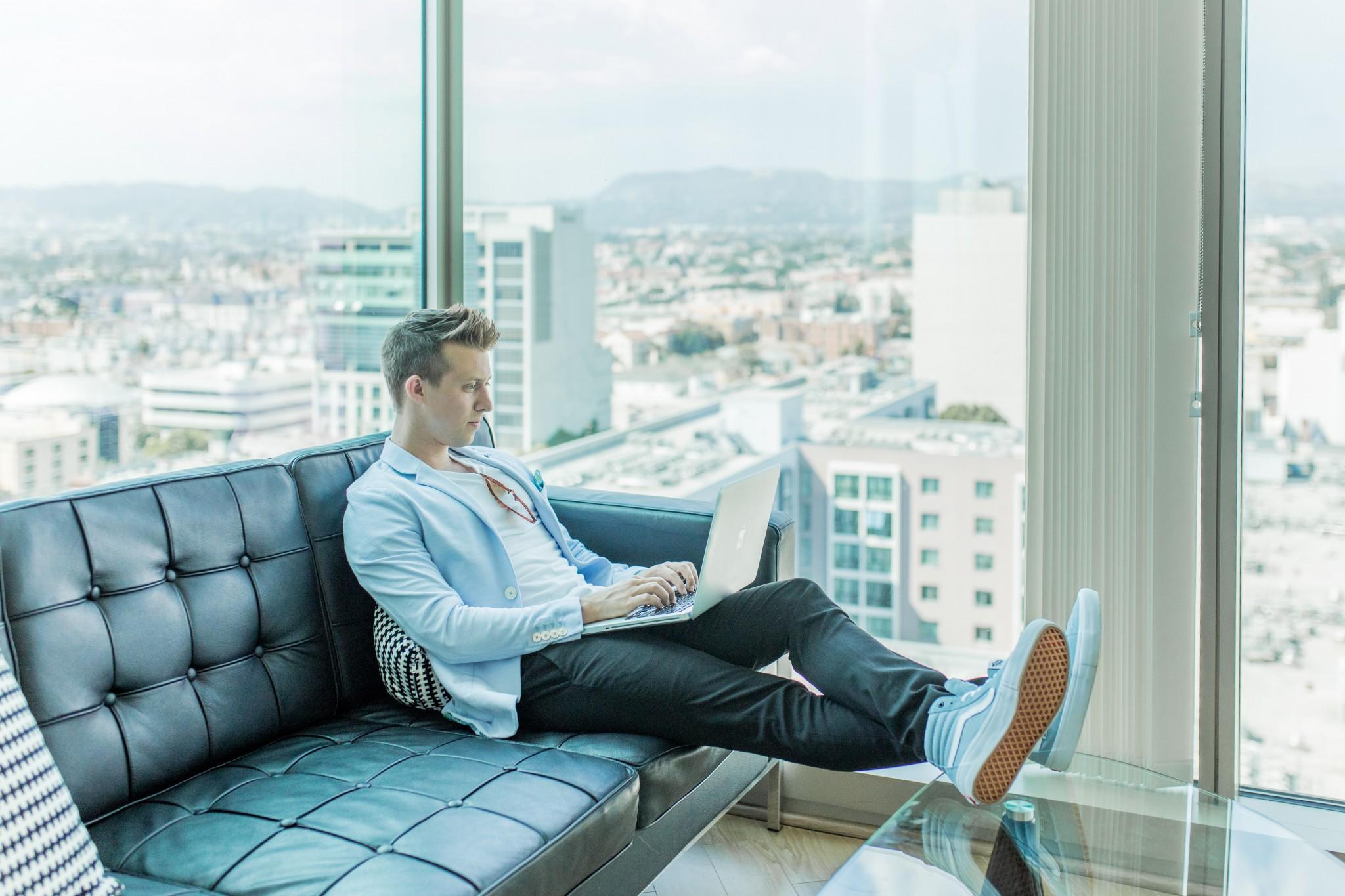 Ragazzo sul divano che scrive al computer